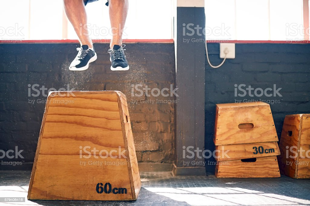 Male athlete is in mid-air over box jump at gym stock photo