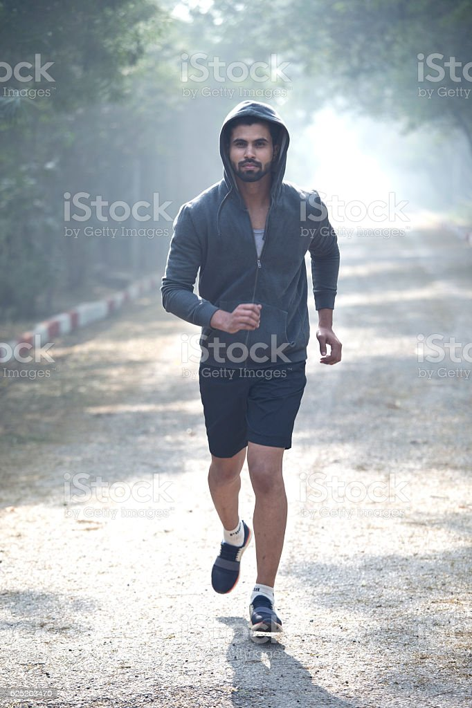 Male athlete jogging at park stock photo