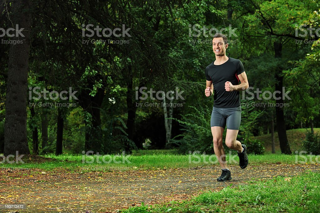 Male athlete jogging on a trail in the park royalty-free stock photo