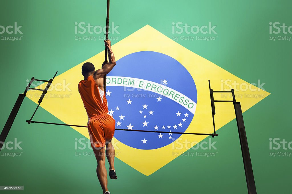 Male athlete jumping over bar against Brazilian flag royalty-free stock photo