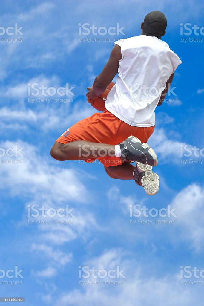 Male Athlete Jumping With Basketball - Sky Background royalty-free stock photo