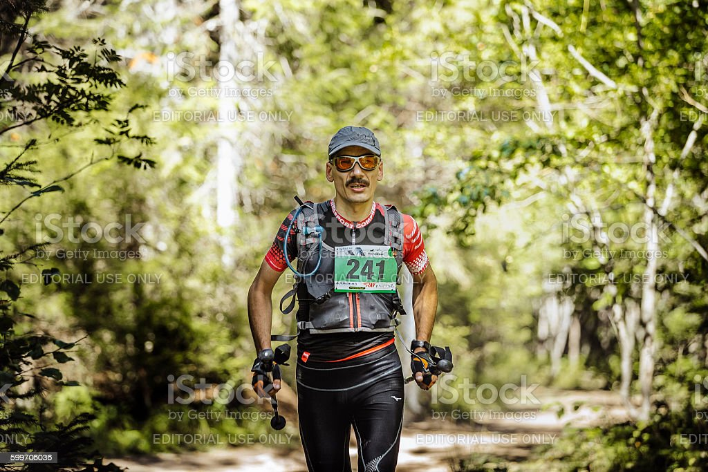 male athlete midlife age runs in woods with nordic poles royalty-free 스톡 사진