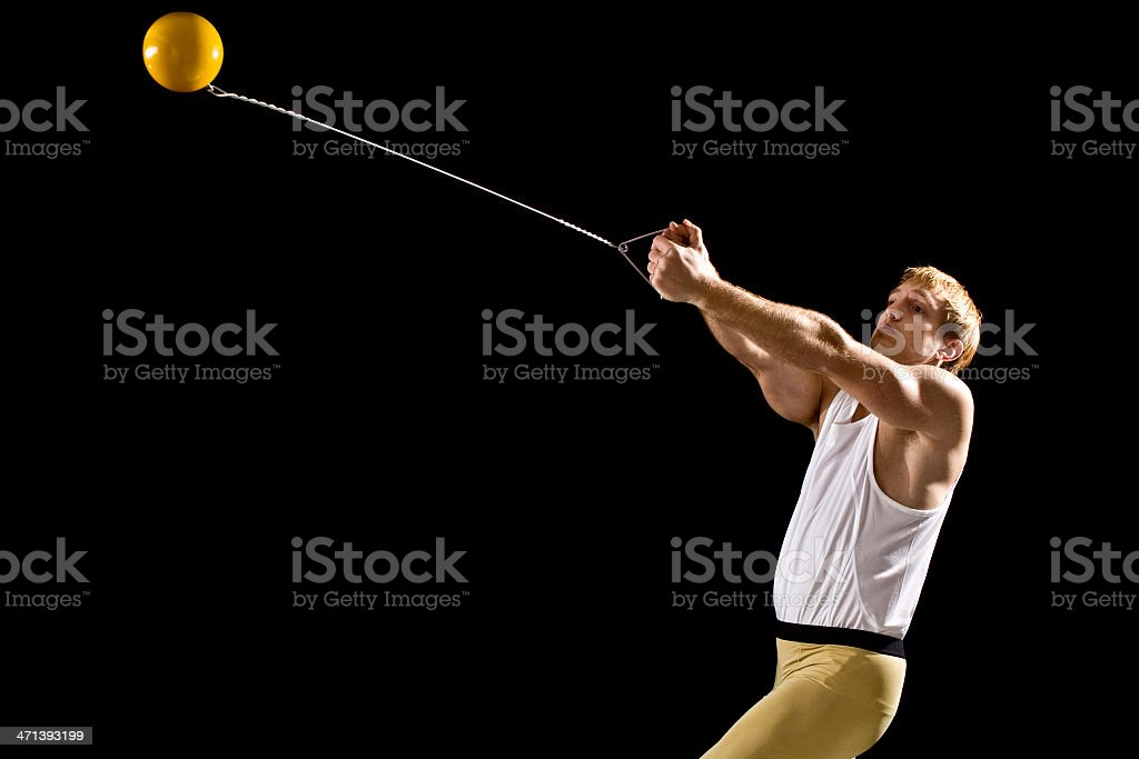 Male athlete on black background doing a hammer throw stock photo