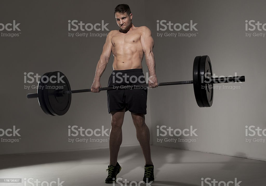male athlete performing clean and jerk with barbell stock photo