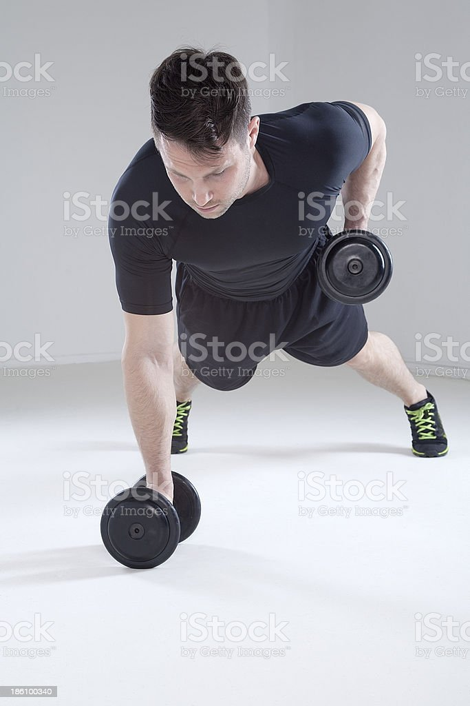 Male athlete performing push up on barbell royalty-free stock photo