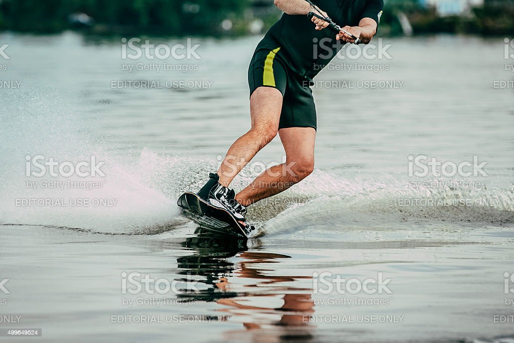 male athlete rides on a wakeboard stock photo