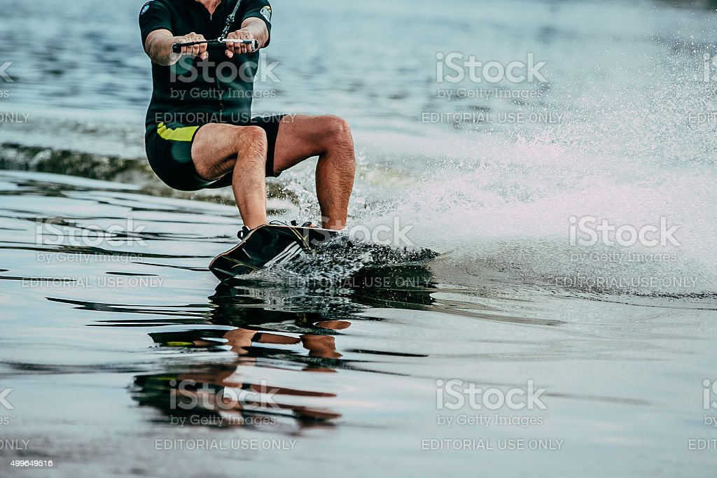 male athlete rides on a wakeboard wave stock photo
