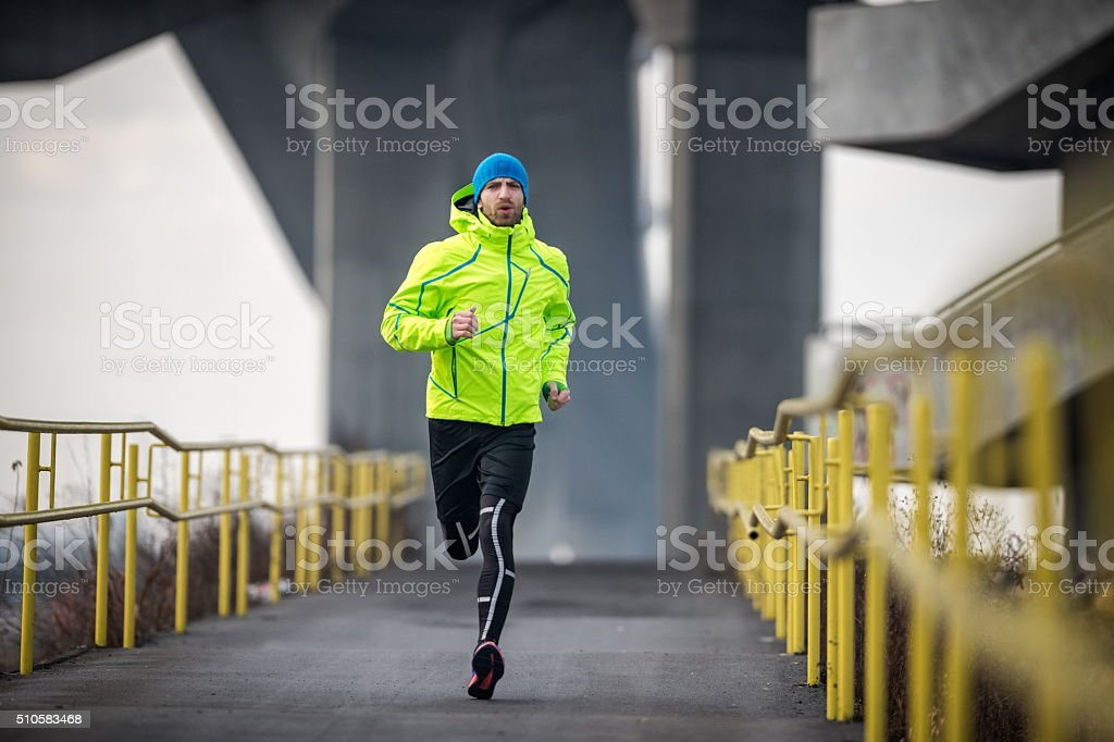 Male athlete running over the bridge stock photo
