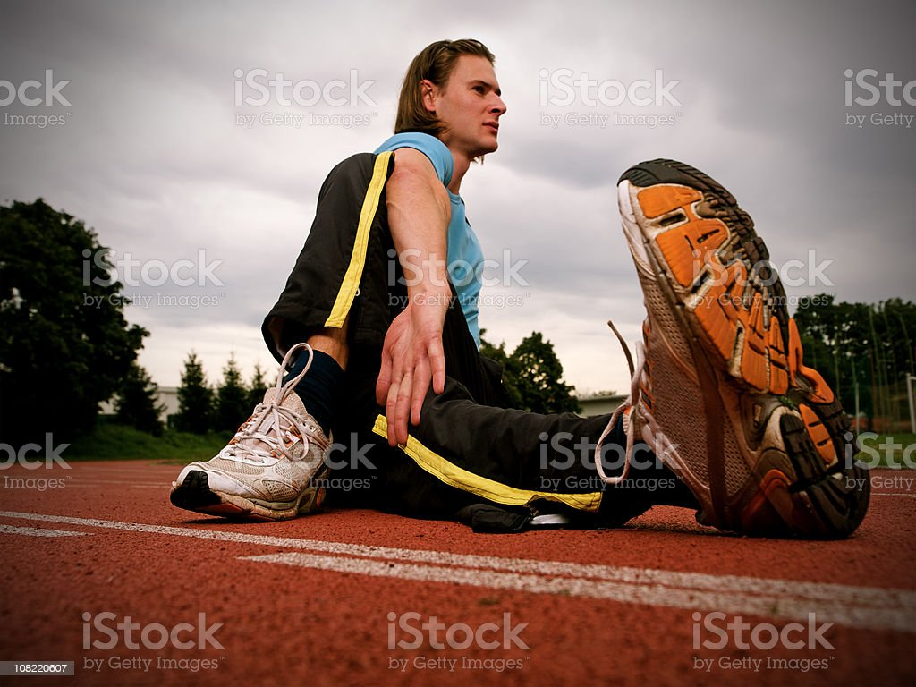 Male athlete sitting on track royalty-free stock photo