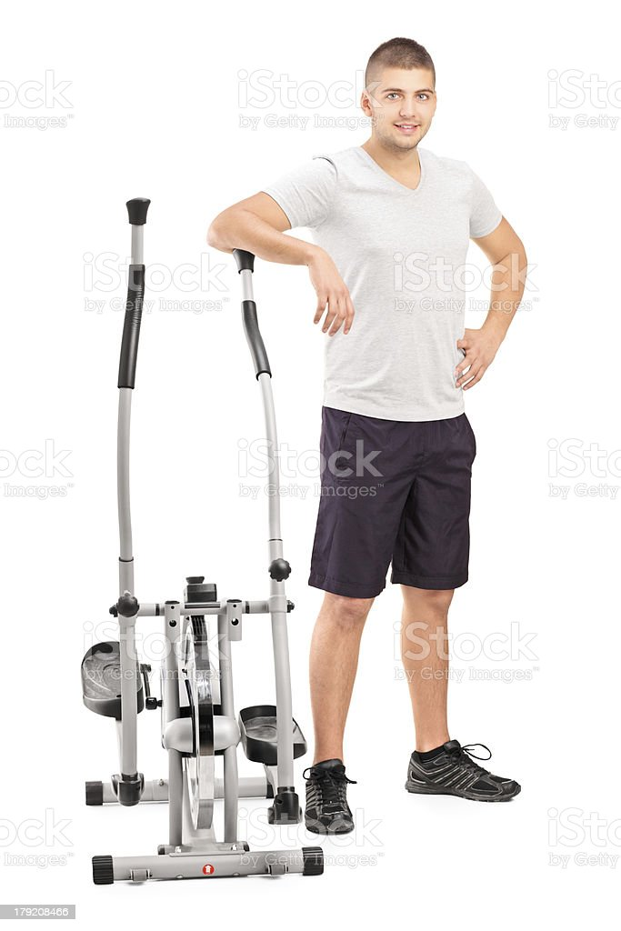 Male athlete standing next to a cross trainer machine royalty-free stock photo