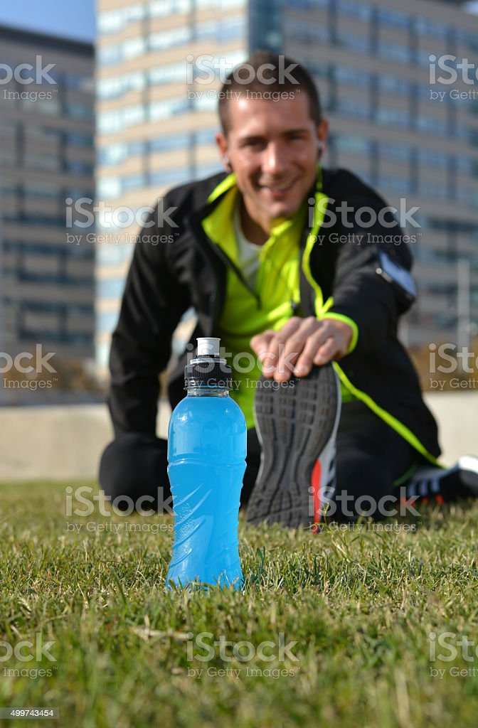 male athlete stretching legs stock photo