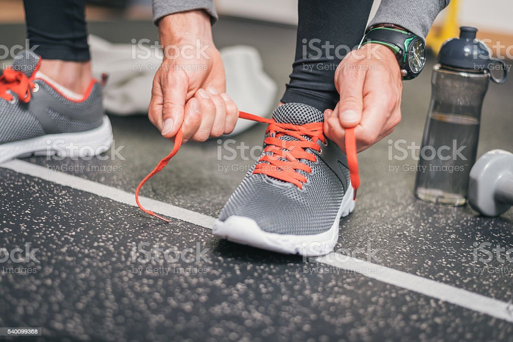 Male athlete tying sport shoes laces before training stock photo