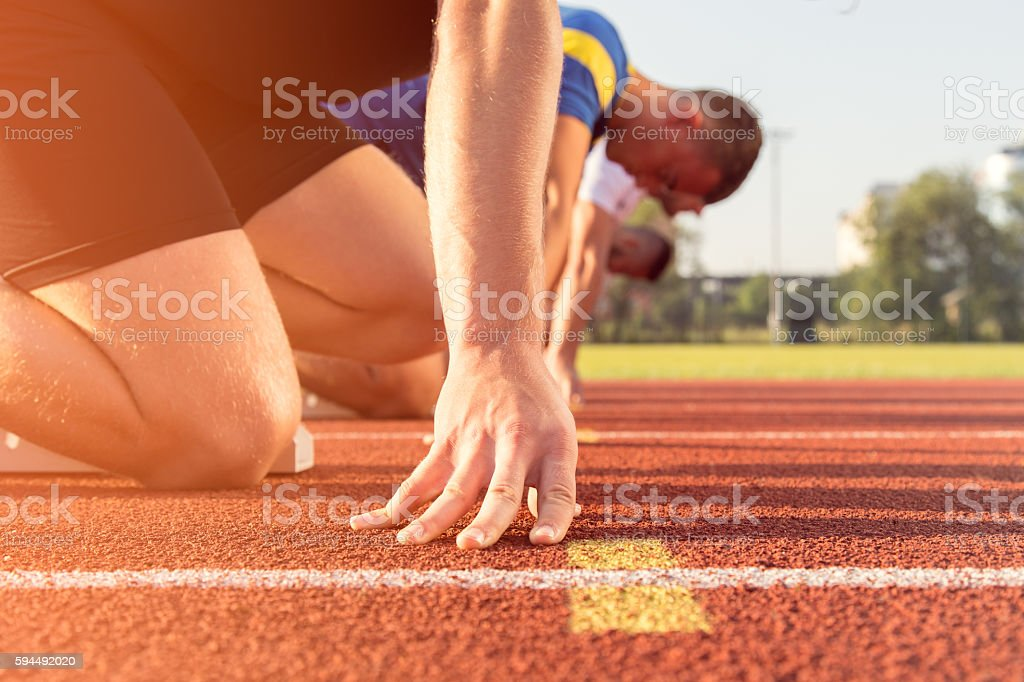 Male athletes at starting line stock photo