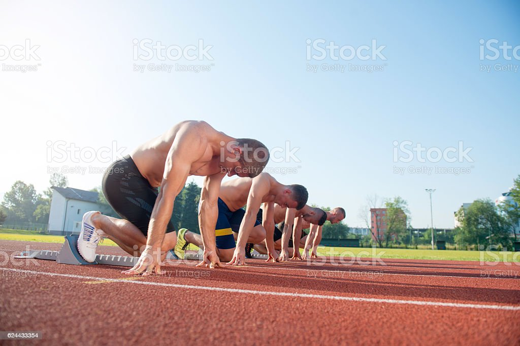 Male athletics runners on starting line without shirts. stock photo