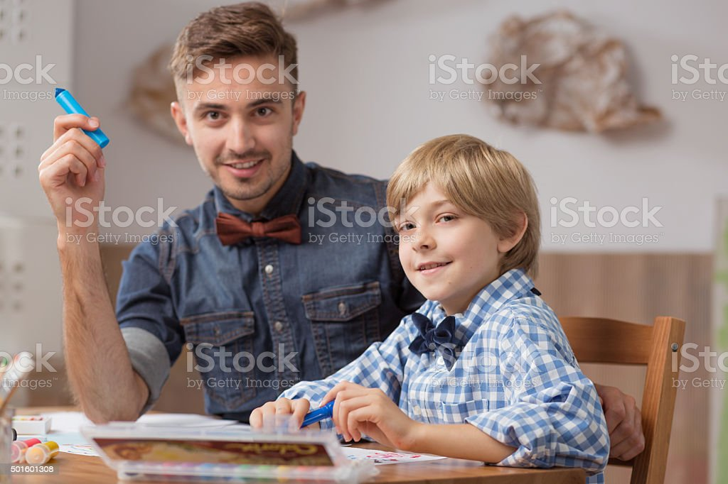 Male babysitter with boy drawing stock photo