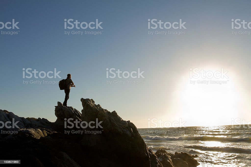 Male Backpacker at Rocky Beach stock photo