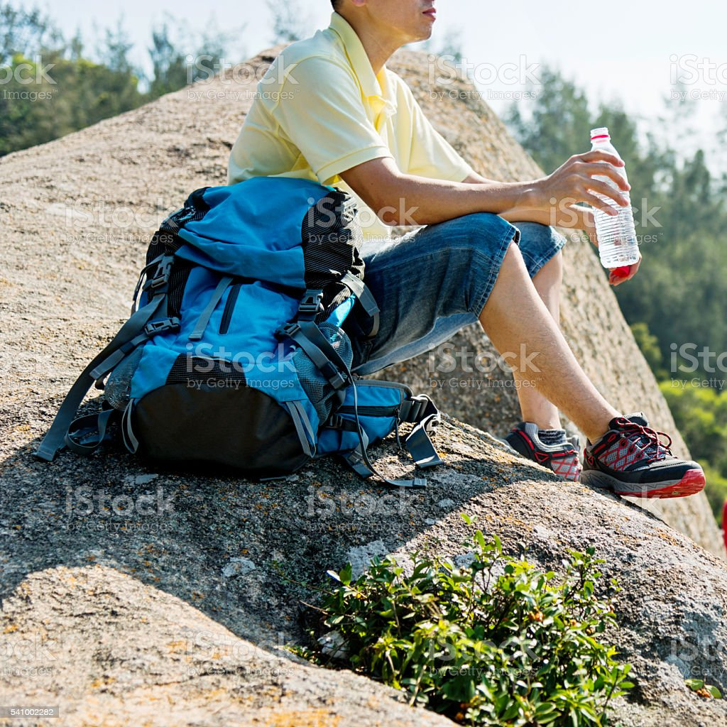 Male backpacker sitting on ledge stock photo