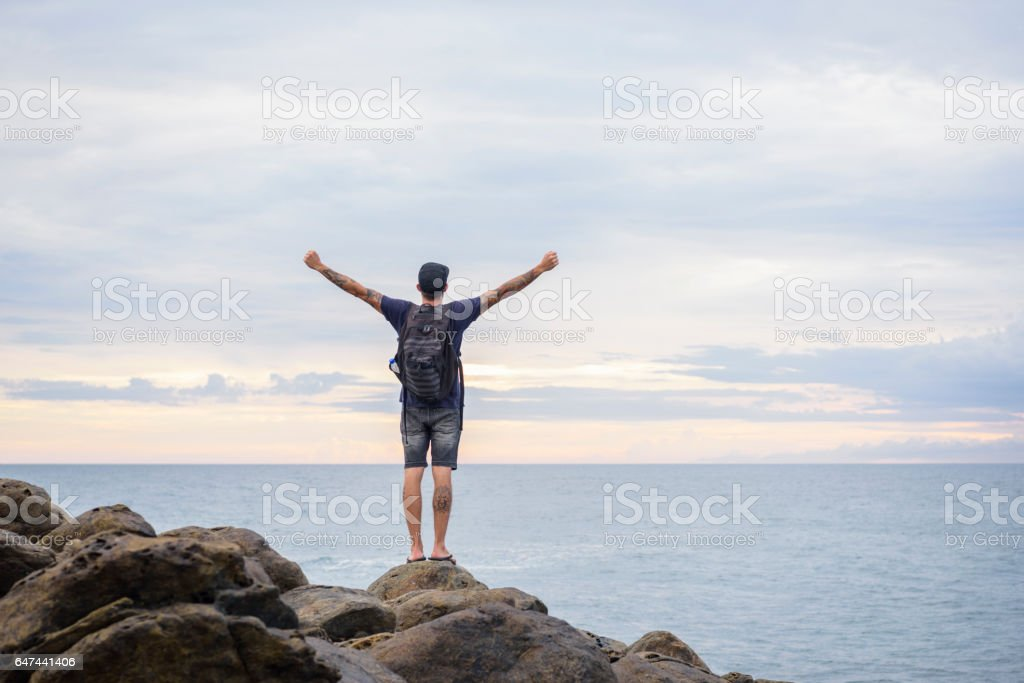 Male backpacker standing on rocks with arms outstretched stock photo