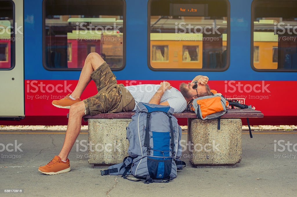 Male backpacker tourist napping on a bench stock photo