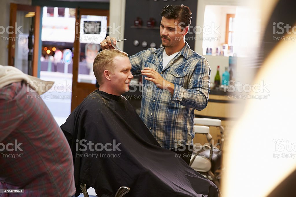 Male Barber Giving Client Haircut In Shop stock photo