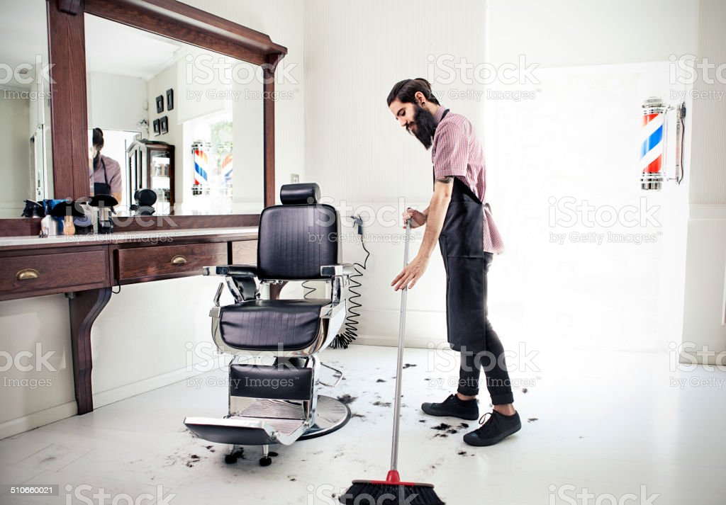 Male barber sweeping floor stock photo