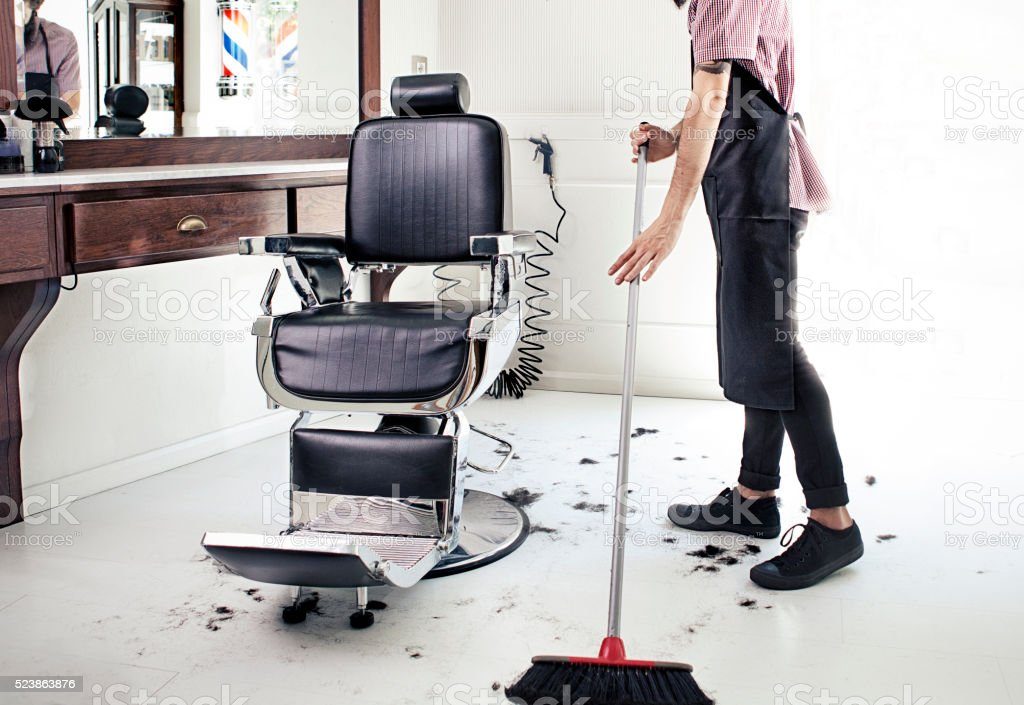 Male barber sweeping floor stock photo