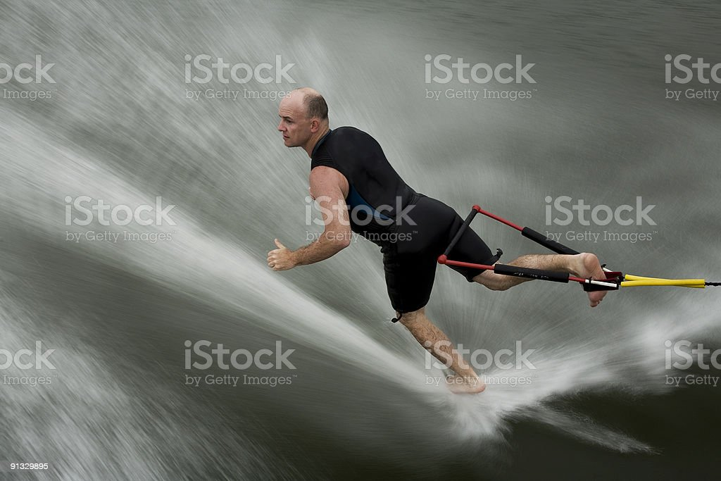 male barefoot water skiing backwards stock photo