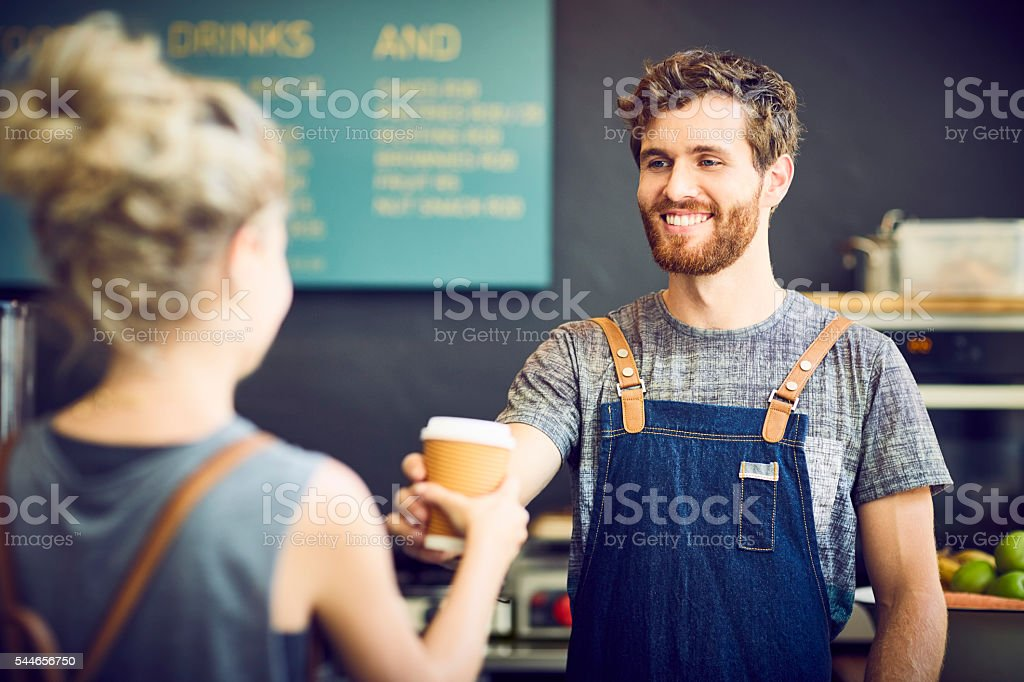 Male barista giving disposable cup to waitress stock photo