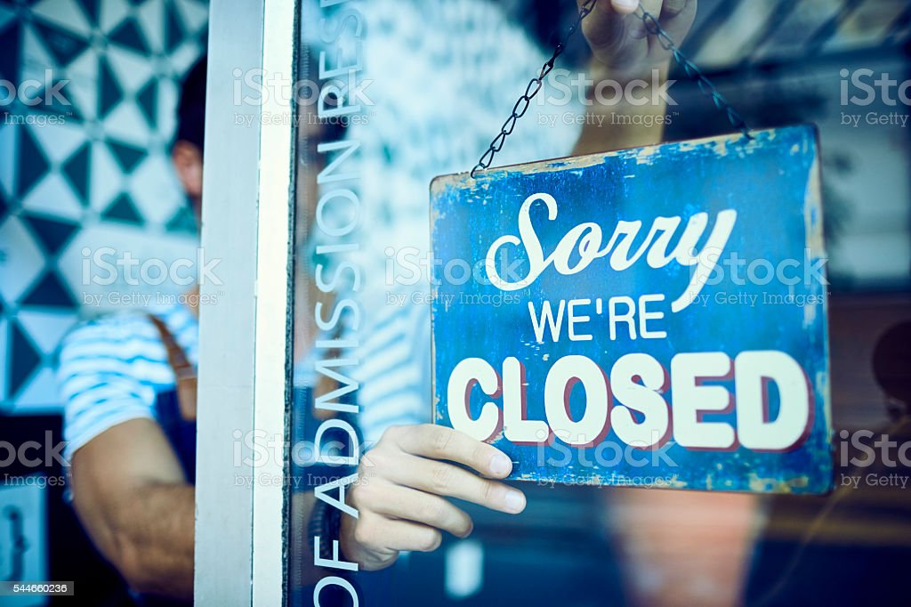 Male barista hanging closed sign on glass stock photo