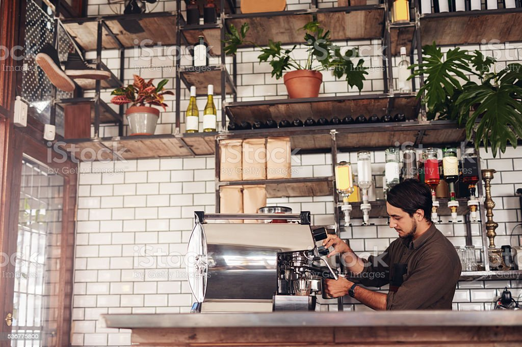 Male barista making a cup of coffee stock photo