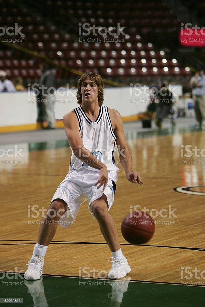 Male Basketball Player Executes NoLook Bounce Pass royalty-free stock photo