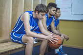 Male basketball players waiting for a game to start