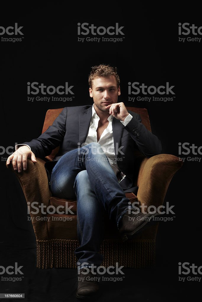 Male Beauty sitting on Armchair. Color Image stock photo