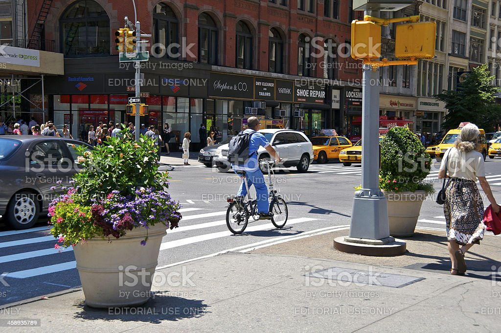 'Male Bicyclist & pedestrians at E.23rd St, Manhattan, NYC' stock photo