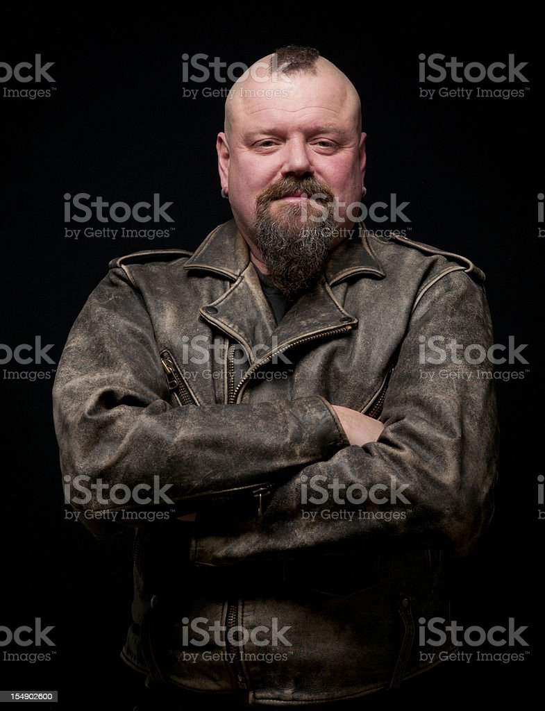 Male biker in a leather coat with his arms crossed royalty-free stock photo