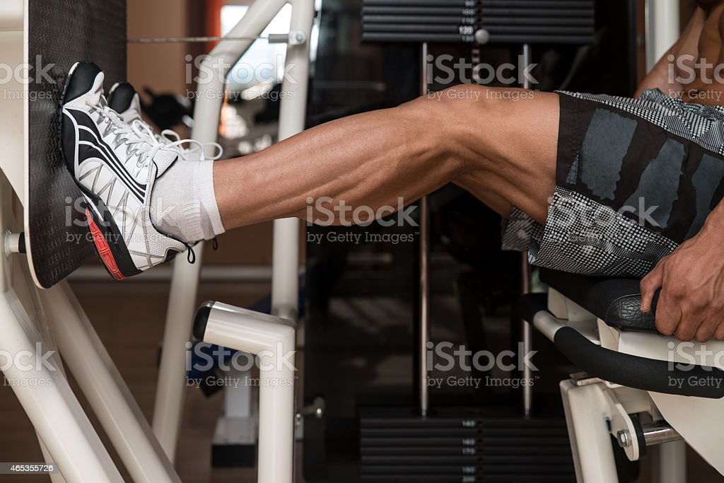 Male bodybuilder performing a seated leg press at the gym stock photo