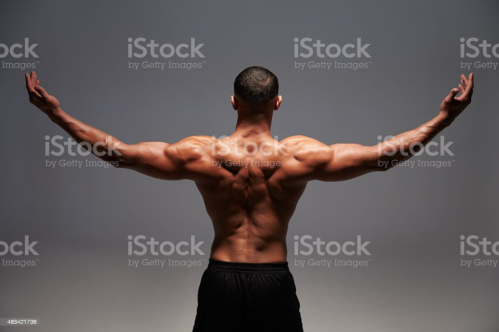Male bodybuilder raising his arms, back view stock photo