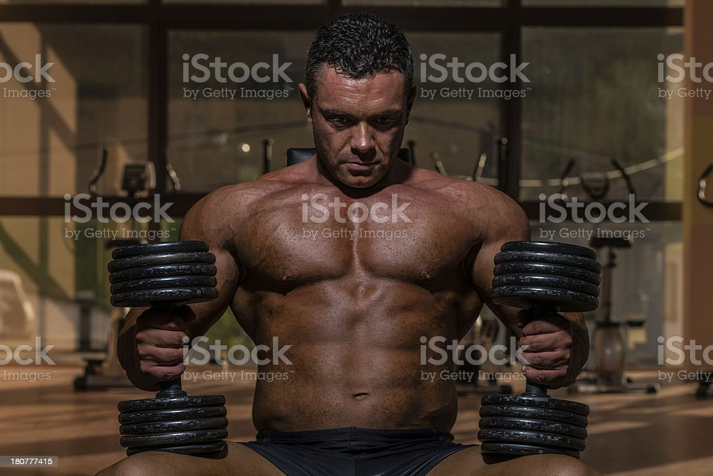 male bodybuilder resting after doing heavy weight exercise royalty-free stock photo