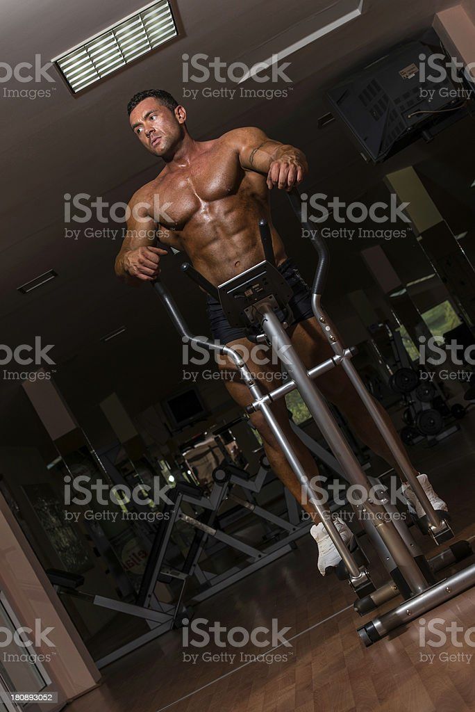 male bodybuilder using the elliptical machine royalty-free stock photo