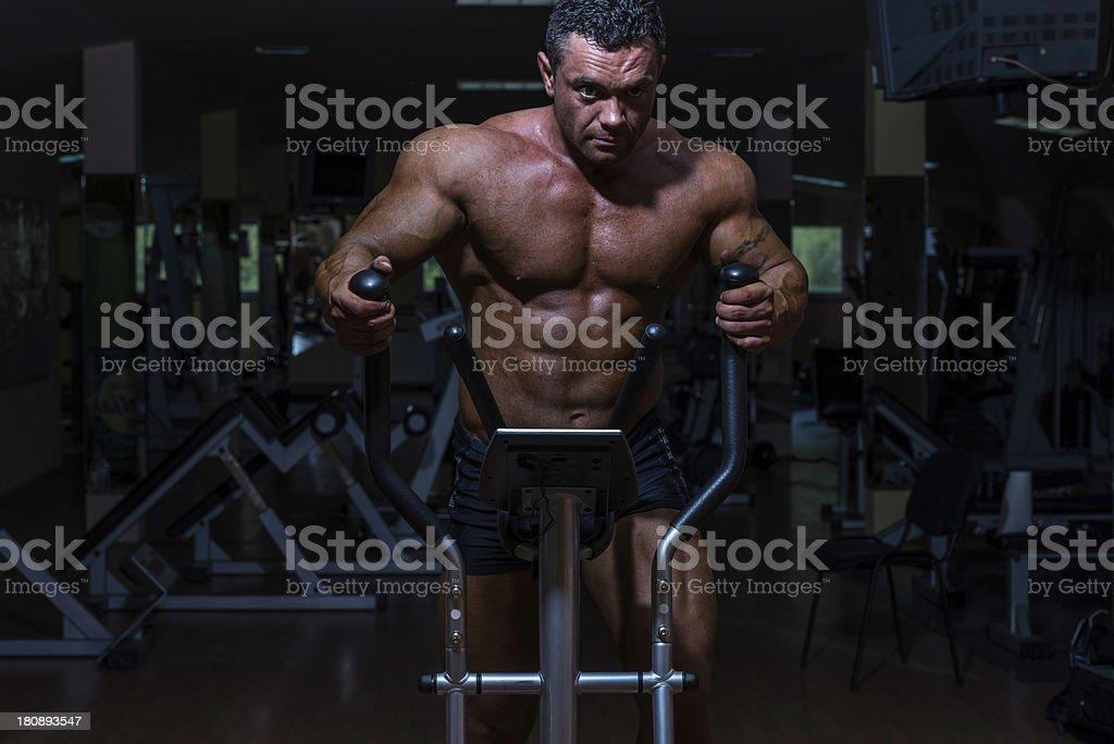 male bodybuilder using the elliptical machine royalty-free stock photo