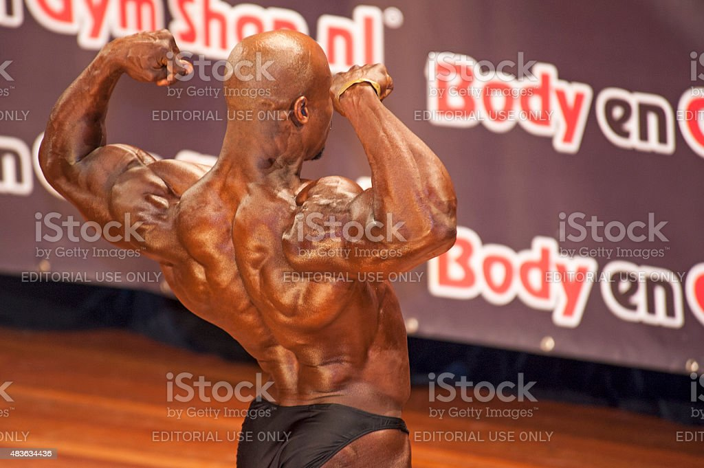 Male bodybuilders showing his best back double biceps pose stock photo