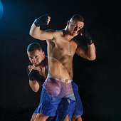 Male boxer boxing in a dark studio