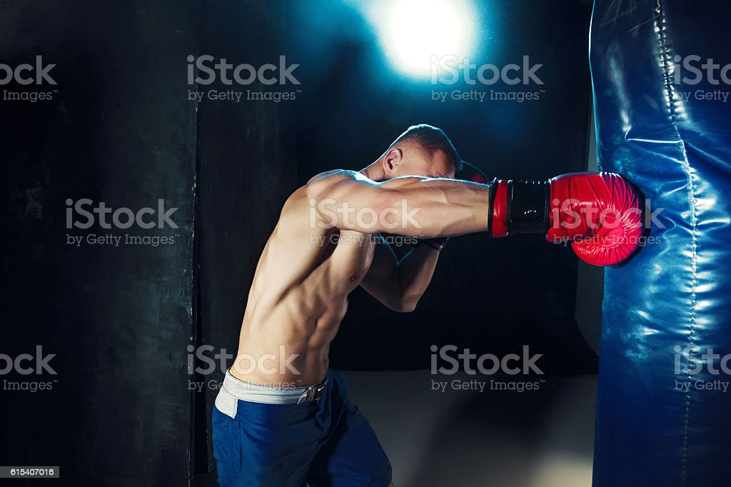 Male boxer boxing in punching bag with dramatic edgy lighting stock photo