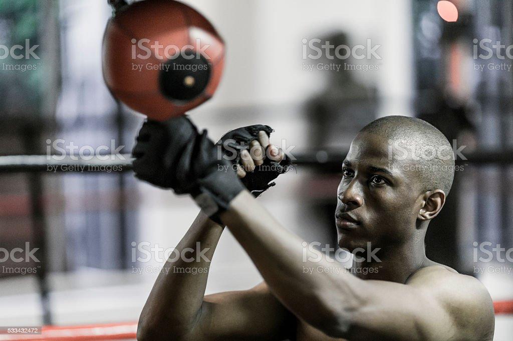 Male boxer punching speed bag stock photo