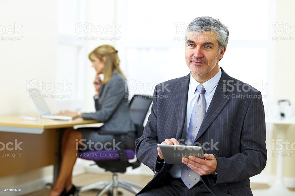 Male business executive with tablet PC looking away in office royalty-free stock photo
