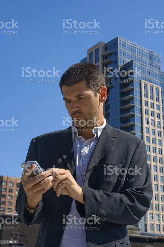 Male Businessman Looking at Smartphone in Outdoor Urban Environment royalty-free stock photo