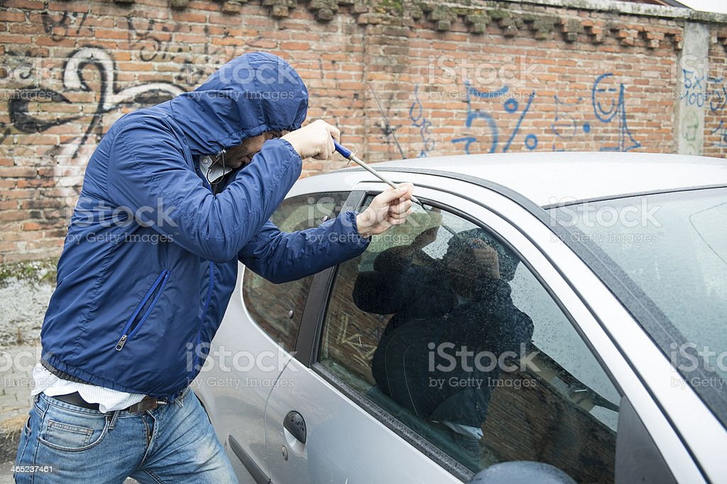 Male car thief in blue jacket breaking into a car stock photo