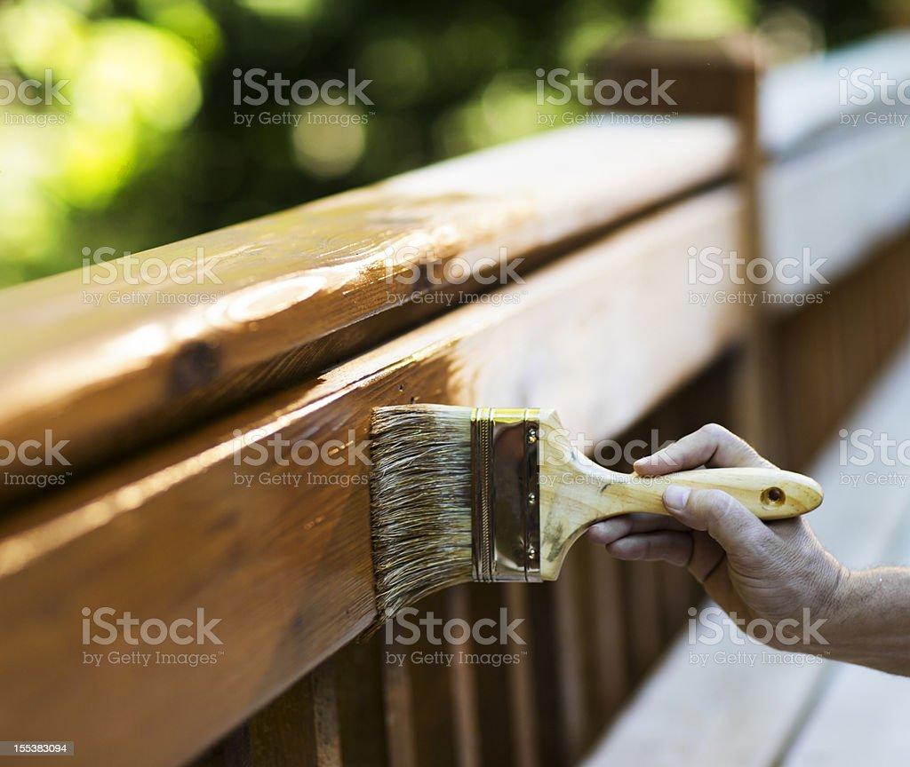 Male Carpenter Applying Varnish To Wooden Furniture. royalty-free stock photo