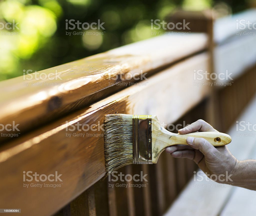 Male Carpenter Applying Varnish To Wooden Furniture. stock photo