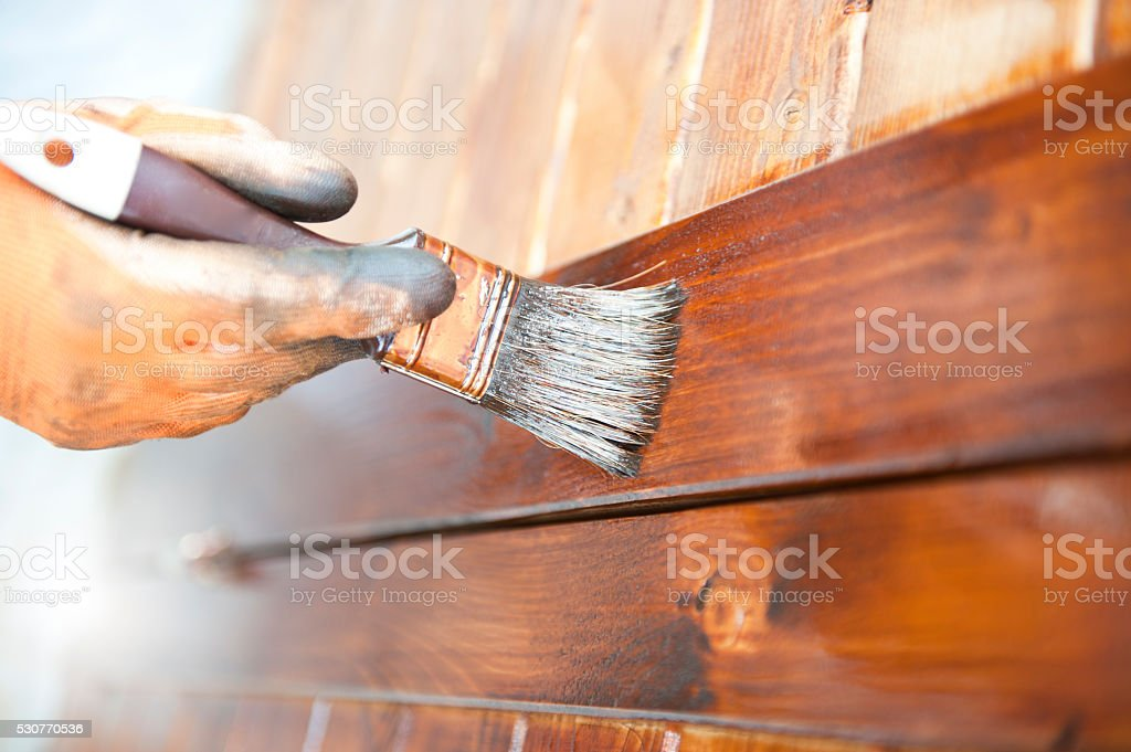 Male Carpenter Applying Varnish To Wooden Furniture stock photo